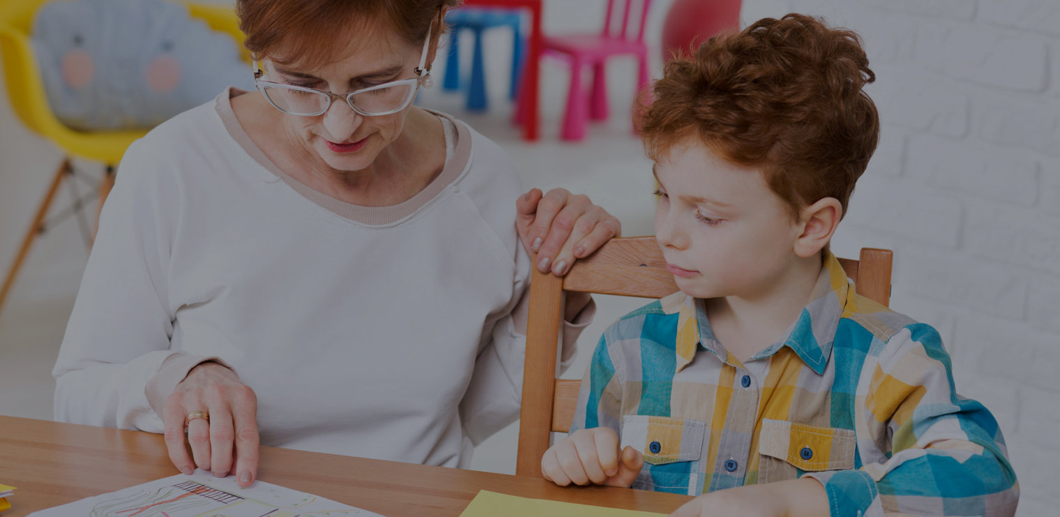 young boy learning new words assisted by his teacher